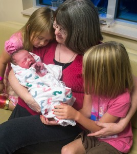 My mom holds Bethany for the first time while Rachel and Sarah look on